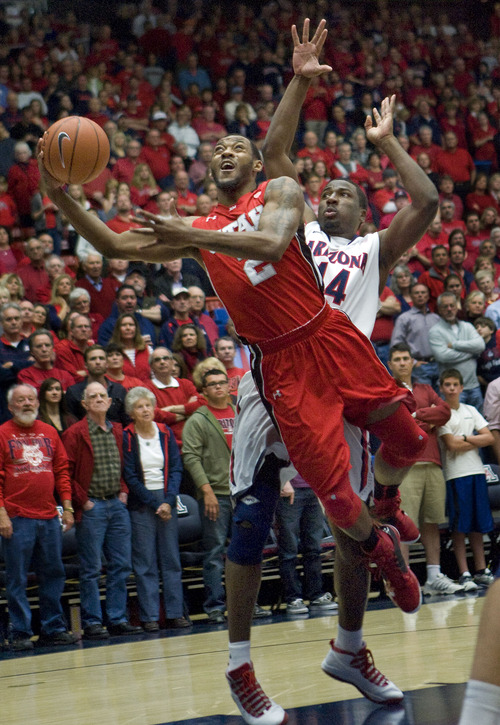 Utah's Aaron Dotson (2) shoots the ball around Arizona's Solomon Hill during the first half of an NCAA college basketball game at McKale Center in Tucson, Ariz., Saturday, Jan. 5, 2013. (AP Photo/Wily Low)