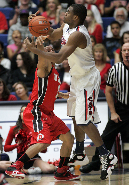 Arizona's Kevin Parrom, right, struggles with Utah's Glen Dean, left, for control of a loose ball during the first half of an NCAA college basketball game at McKale Center in Tucson, Ariz., Jan.5, 2013. (AP Photo/John Miller)