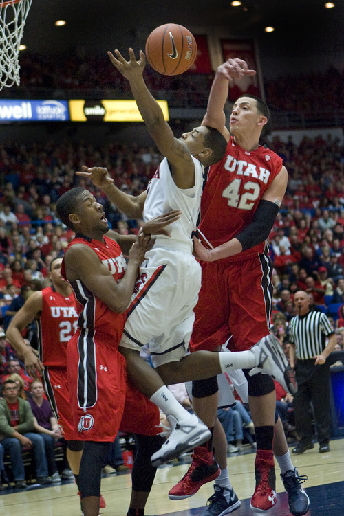 Arizona's Mark Lyons, center, tries to shoots between Utah's Jason Washburn (42) and Jarred Dubois, left, during the second half of an NCAA college basketball game at McKale Center in Tucson, Ariz., Saturday, Jan. 5, 2013. Arizona won 60-57. (AP Photo/Wily Low)