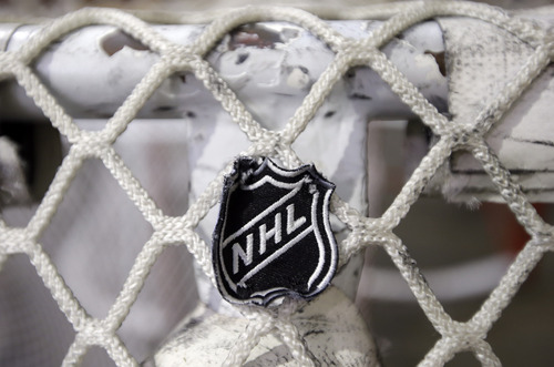 FILE - In this file photo taken Sept. 17, 2012, the NHL logo is seen on a goal at a Nashville Predators practice rink in Nashville, Tenn.  (AP Photo/Mark Humphrey, file)