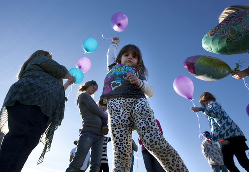 Steve Griffin |  The Salt Lake Tribune LuLu Badger stretches as she holds a balloon that will be released in memory of Ashley Maynard at the Vernal Cemetery in Vernal, Utah, Saturday, October 27, 2012. Ashley, 12, died in 2010 after darting in front of a car on her way to catch a school bus. Ashley's family donated her organs. and her liver saved the LuLu's life.