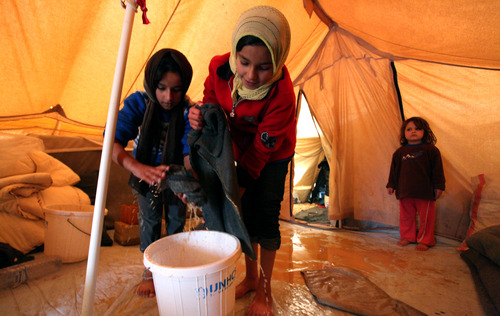 Syrian refugee girls remove water and mud from their tent after a flood at Zaatari Syrian refugee camp, near the Syrian border in Mafraq, Jordan, Tuesday, Jan. 8, 2013. Syrian refugees in a Jordanian camp attacked aid workers with sticks and stones on Tuesday, frustrated after cold, howling winds swept away their tents and torrential rains flooded muddy streets overnight. Police said seven aid workers were injured. (AP Photo/Mohammad Hannon)