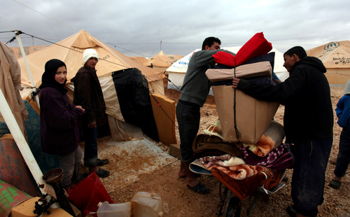 Syrian refugees get their belongings out of their tent at Zaatari Syrian refugee camp, near the Syrian border in Mafraq, Jordan, Tuesday, Jan. 8, 2013. Syrian refugees in a Jordanian camp attacked aid workers with sticks and stones on Tuesday, frustrated after cold, howling winds swept away their tents and torrential rains flooded muddy streets overnight. Police said seven aid workers were injured. (AP Photo/Mohammad Hannon)