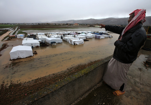 A Syrian refugee points towards the temporary refugee camp which was flooded by rain, in the eastern Lebanese Town of Al-Faour near the border with Syria, Lebanon ,Tuesday, Jan. 8, 2013. Two Syrian refugee encampments in Lebanon's eastern Bekaa valley  were completely immersed in water Tuesday after the Litani river flooded and the water came pouring into their tents. The flood forced dozens of Syrian refugees to leave in search for alternative shelter along with their water-soaked and muddied belongings. (AP Photo/Hussein Malla)