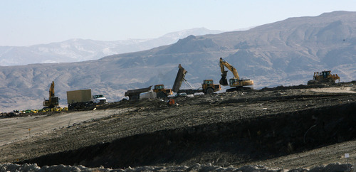 Steve Griffin | The Salt Lake Tribune  Heavy equipment is used to bury waste at EnergySolutions' low-level radioactive waste landfill in Clive, Utah. The company is being sold to private equity firm and some environmental watchdogs worry about what that will mean for the site.