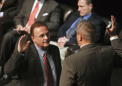Al Hartmann  |  The Salt Lake Tribune Salt Lake County Councilman Max Burdick, left, takes the oath of office from outgoing Utah Attorney General Mark Shurtleff at the Rose Wagner Theatre Monday January 7.