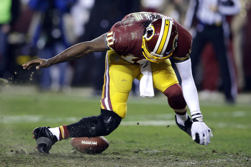 Washington Redskins quarterback Robert Griffin III twists his knees as he reaches for the loose ball after a low snap during the second half of an NFL wild card playoff football game against the Seattle Seahawks in Landover, Md., Sunday, Jan. 6, 2013. (AP Photo/Matt Slocum)