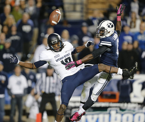 Utah State's Mitch Mathews, left, has his catch broken up by  BYU's Jordan Johnson during the second half of an NCAA college football game at LaVell Edwards Stadium, Friday, Oct. 5, 2012, in Provo, Utah. BYU beat Utah Sate 6-3. (AP Photo/George Frey)