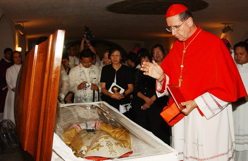 In this handout photo released by the Archdiocese of Manila, Cardinal Roger Mahoney of Los Angeles, California blesses the remians of influential Cardinal Jaime Sin before his burial at Manila's Cathedral on June 28, 2005. Mahony was a strong proponent of social justice and Cardinal Sin was a beloved spiritual leader who rallied the nation to massive pro-democracy protests that ousted two presidents. (AP Photo/Archdiocese of Manila, Noli Yamsuan, HO)