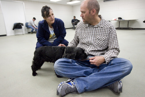 Kim Raff     The Salt Lake Tribune (left) Renee Olsen, an Army National Guard veteran of Desert Storm, works with her dog, Lucy, and class instructor Shaun Woodard during an exercise at Canines With A Cause class at Northwest Recreation Center in Salt Lake City on December 21, 2012. Canines With A Cause is a non-profit that trains veterans and their dogs.