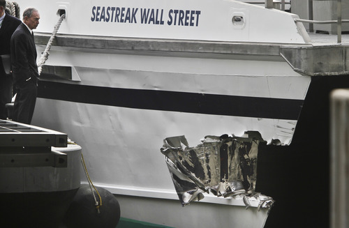 Mayor Michael Bloomberg surveys the damage to a passenger ferry after it crashed on Wednesday, Jan. 9, 2013 in New York.  At least 57 people were injured, two critically, when a commuter ferry struck a dock in New York City's financial district, ripping open a right-side front corner. (AP Photo/Bebeto Matthews)