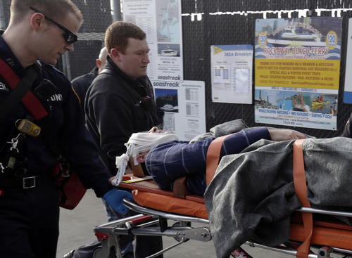 An injured passenger from the Seastreak Wall Street is taken to an ambulance, in New York,  Wednesday, Jan. 9, 2013. The Seastreak Wall Street ferry from Atlantic Highlands, N.J., banged into the mooring as it arrived at South Street in lower Manhattan during morning rush hour, injuring as many as 50 people, at least one critically, officials said.(AP Photo/Richard Drew)