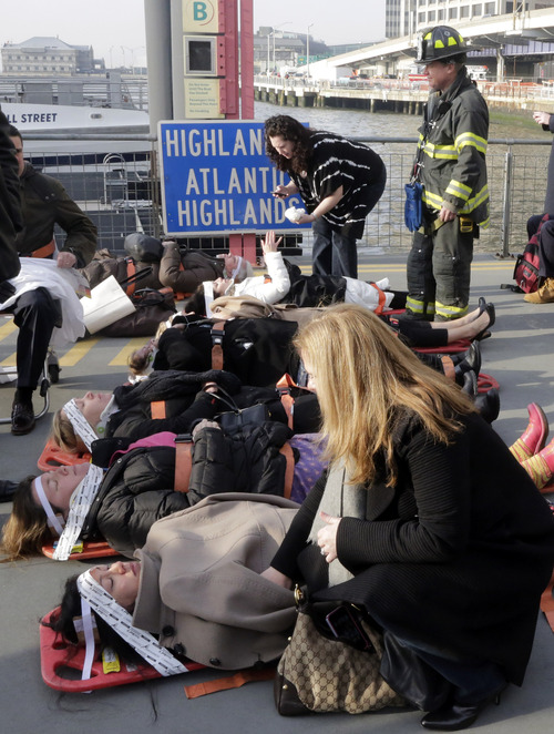 Injured passengers from the Seastreak Wall Street ferry wait to be taken to ambulances, in New York,  Wednesday, Jan. 9, 2013. The ferry from Atlantic Highlands, N.J., banged into the mooring as it arrived at South Street in lower Manhattan during morning rush hour, injuring as many as 50 people, at least one critically, officials said.(AP Photo/Richard Drew)