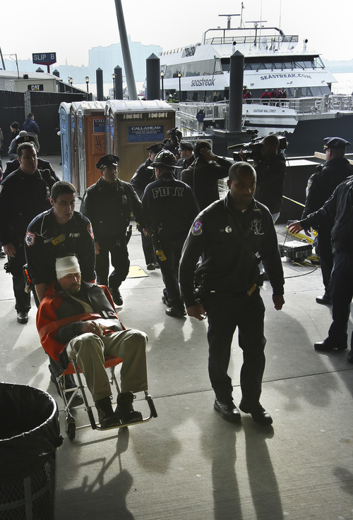 Paramedics wheel an injured ferry passenger away after the boat crashed on Wednesday, Jan. 9, 2013 in New York.  At least 57 people were injured, two critically, when a commuter ferry struck a dock in New York City's financial district, ripping open a right-side front corner. (AP Photo/Bebeto Matthews)