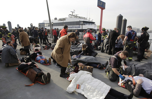 Victims of the Seastreak Wall Street ferry accident are aided by rescue personnel, Wednesday, Jan. 9, 2013 in New York. The ferry, rear, from New Jersey made a hard landing at the dock as it pulled up to lower Manhattan during Wednesday morning rush hour, injuring as many as 50 people, at least one critically, officials said. (AP Photo/Mark Lennihan)