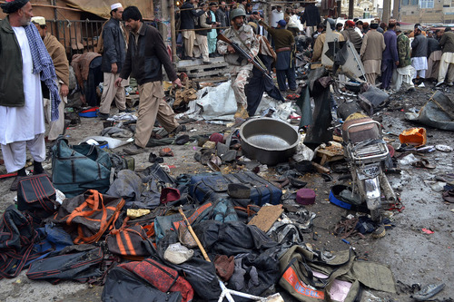 A Pakistani paramilitary soldier and local residents gather at the site of a bomb blast that targeted paramilitary soldiers in a commercial area in Quetta, Pakistan, killing at least 12 people and wounding more than 40 others, according to police, Thursday, Jan. 10, 2013. A series of bombings in different parts of Pakistan killed 115 people on Thursday in one of the deadliest days in the country in recent years. (AP Photo/Arshad Butt)