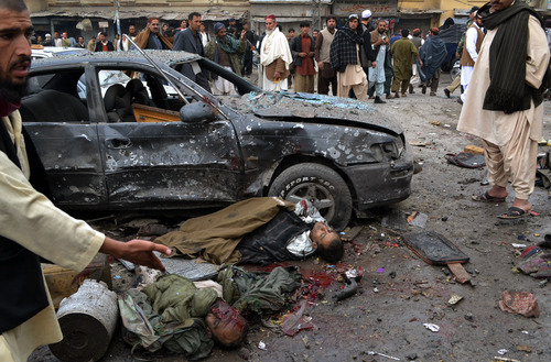 EDS NOTE: GRAPHIC CONTENT - A Pakistani gestures towards two dead bodies at the site of bomb blast in Quetta, Pakistan, Thursday, Jan. 10, 2013. A bomb targeting paramilitary soldiers killed scores of people in southwest Pakistan, officials said. (AP Photo/Arshad Butt)