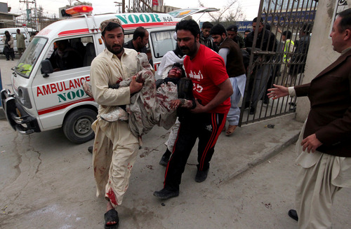 CORRECTS THE NUMBER OF PEOPLE KILLED IN THIS BOMBING INCIDENT TO 12, NOT SCORES. ADDS THAT THERE WERE A SERIES OF BOMBINGS IN DIFFERENT PARTS OF PAKISTAN THURSDAY, KILLING AT LEAST 115 PEOPLE. - Pakistani volunteers rush an injured victim from a bomb blast in a commercial area to a local hospital in Quetta, Pakistan, Thursday, Jan. 10, 2013. The bomb targeting paramilitary soldiers killed at least 12 people and wounded more than 40 others, according to a senior police official. A series of bombings in different parts of Pakistan killed 115 people on Thursday in one of the deadliest days in the country in recent years. (AP Photo/Arshad Butt)