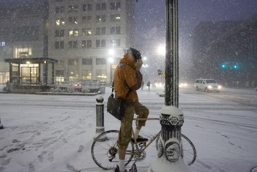 Kim Raff | The Salt Lake Tribune A bike rider adjusts himself at a cross walk during heavy snow on Main Street during the evening commute in downtown Salt Lake City on January 10, 2013.
