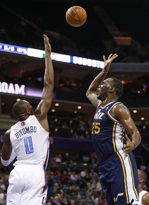 Utah Jazz's Al Jefferson (25) shoots over Charlotte Bobcats' Bismack Biyombo (0) during the first half of an NBA basketball game in Charlotte, N.C., Wednesday, Jan. 9, 2013. The Jazz won 112-102. (AP Photo/Chuck Burton)