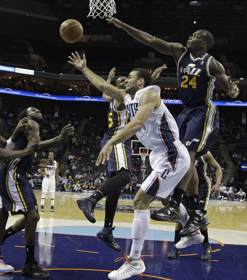 Charlotte Bobcats' Ramon Sessions, center, shoots as he drives on Utah Jazz's Paul Millsap, right, DeMarre Carroll, left, and Al Jefferson, back, during the first half of an NBA basketball game in Charlotte, N.C., Wednesday, Jan. 9, 2013. (AP Photo/Chuck Burton)
