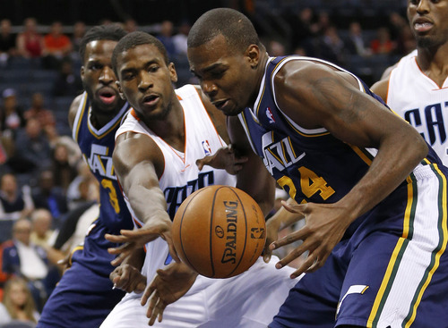 Utah Jazz's Paul Millsap, right, and Charlotte Bobcats' Michael Kidd-Gilchrist, left, chase a loose ball during the first half of an NBA basketball game in Charlotte, N.C., Wednesday, Jan. 9, 2013. (AP Photo/Chuck Burton)