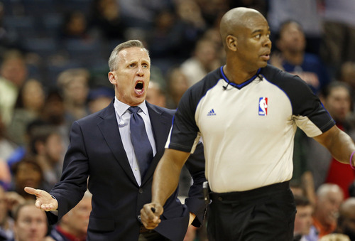 Charlotte Bobcats head coach Mike Dunlap, left, shouts at referee Sean Wright, right, during the second half of an NBA basketball game against the Utah Jazz in Charlotte, N.C., Wednesday, Jan. 9, 2013. The Jazz won 112-102. (AP Photo/Chuck Burton)