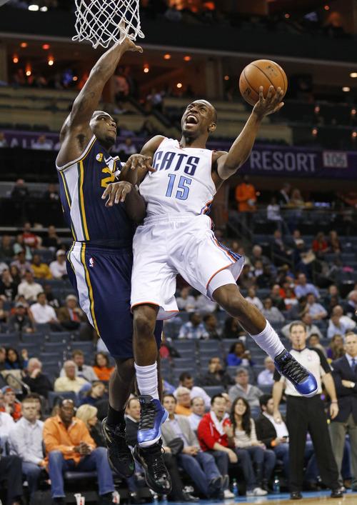 Charlotte Bobcats' Kemba Walker, right, drives on Utah Jazz's Paul Millsap, left, during the second half of an NBA basketball game in Charlotte, N.C., Wednesday, Jan. 9, 2013. The Jazz won 112-102. (AP Photo/Chuck Burton)
