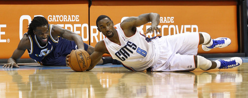 Charlotte Bobcats' Ben Gordon, right, and Utah Jazz's DeMarre Carroll, left, scramble for control of a loose ball during the second half of an NBA basketball game in Charlotte, N.C., Wednesday, Jan. 9, 2013. The Jazz won 112-102. (AP Photo/Chuck Burton)