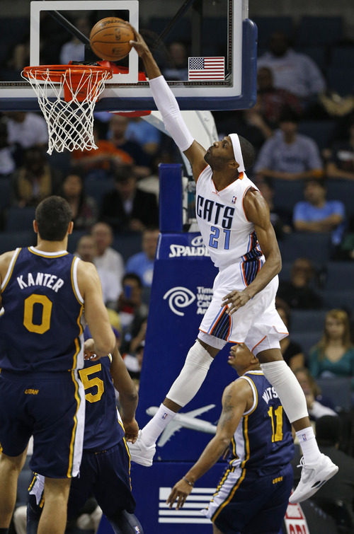 Charlotte Bobcats' Hakim Warrick (21) dunks as Utah Jazz's Enes Kanter (0) looks on during the first half of an NBA basketball game in Charlotte, N.C., Wednesday, Jan. 9, 2013. (AP Photo/Chuck Burton)