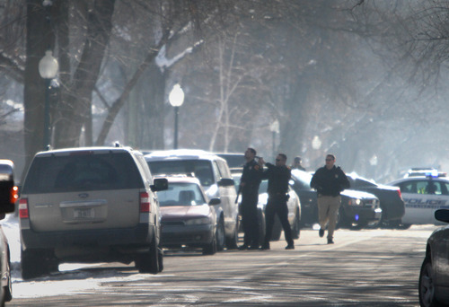 Rick Egan  | The Salt Lake Tribune   Police officers have their guns ready, on 800 set between 800 and 900 south in Salt Lake, Wednesday, January 9, 2013.