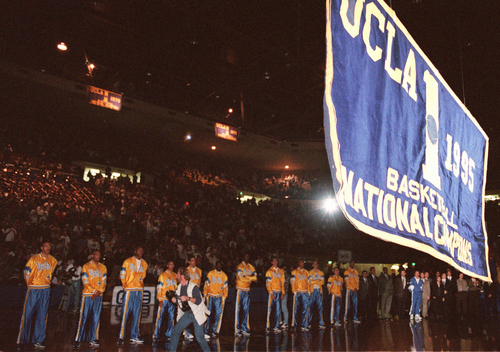 University of California Los Angeles basketball team players line up under a banner being unveiled at the UCLA Pauley Pavilion Tuesday, Nov. 28, 1995 in Los Angeles, to commemorate their winning title as National Champions in 1995. (AP Photo/Damian Dovarganes)