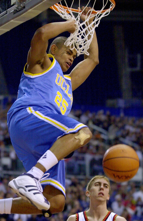 UCLA guard Earl Watson hangs on the rim after dunking the ball during second half action against Maryland in the second round of the men's NCAA basketball tournament in Minneapolis, Saturday, March 18, 2000. (AP Photo/Morry Gash)