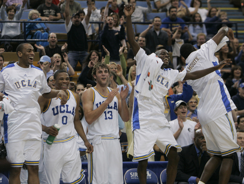 The UCLA bench, from left, starter Arron Afflalo, Russell Westbrook, James Keefe, and starters Darren Collison and Luc Richard Mbah a Moute celebrate as substitutes finish the final minutes of an NCAA Pac-10 basketball game against Oregon state in Los Angeles, Saturday, Feb. 3, 2007. UCLA won, 82-35. (AP Photo/Reed Saxon)