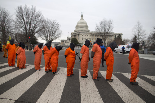 Demonstrators, dressed as detainees, march past the Capitol building on Capitol Hill in Washington, Friday, Jan. 11, 2013, during a rally against the U.S. military detention facility in Guantanamo Bay, Cuba . The protest marks the 11th anniversary of the first detainees being jailed at Guantanamo Bay. (AP Photo/ Evan Vucci)