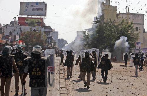 Indian policemen face stones pelted by Muslim supporters of Majlis-e-Ittehadul Muslimeen leader Akbaruddin Owaisi after Friday prayers at Mecca Masjid in Hyderabad, India, Friday, Jan. 11, 2013. Tension prevailed in the old city of Hyderabad Friday after violent protests by a group of people protesting against Owaisi's arrest for his alleged hate speech. Police used batons and tear gas to disperse hundreds of youths coming out of the historic Mecca Masjid after Friday prayers as they resorted to stoning. (AP Photo/Mahesh Kumar A.)