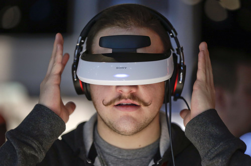 Justin Bredeau, of Las Vegas, tries out a Sony 3-D personal viewer at the Consumer Electronics Show, Friday, Jan. 11, 2013, in Las Vegas. The viewer simulates watching a 150-inch screen from 12 feet away. (AP Photo/Julie Jacobson)