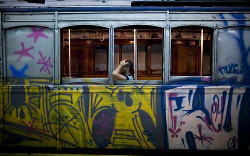 """A passenger travels in a wooden carriage car on Line A of the historic subway in Buenos Aires, Argentina, Friday, Jan. 11, 2013.  The almost 100-year-old """"La Brugeoise"""" wooden carriages will stop working today and be replaced soon by modern Chinese units. The 90 Belgian cars began rolling in 1913 on Latin America's first subway line and are the oldest subway cars still operating in the world, carrying 160,000 passengers on the line daily. (AP Photo/Natacha Pisarenko)"""