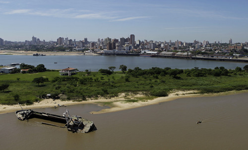 An abandoned cargo ship lays half sunken in the Paraguay River near Asuncion, Paraguay, Friday, Jan. 11, 2013.  The Paraguay River's water level is at an all time low this summer, which makes it difficult for larger ships to cross through its channels and reach the capital city. According to the Customs Office, imports declined 18 percent between 2011 and 2012 due to low water levels. (AP Photo/Jorge Saenz)
