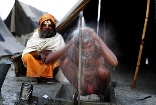An Indian Sadhu or holy man, takes an early morning bath at a camp near Sangam, the confluence of the rivers Ganges, Yamuna and mythical Saraswati, in Allahabad, india, Friday, Jan. 11, 2013. Millions of Hindu pilgrims are expected to take part in the large religious gathering that lasts for more than a month on the banks of Sangam and falls every 12th year. (AP Photo/Rajesh Kumar Singh)