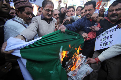 Activists of India's main opposition Bharatiya Janata Party shout slogans and burn a flag of Pakistan during a protest in Jammu, India, Friday, Jan. 11, 2013. India has formally complained about an attack on an Indian army patrol in the disputed Himalayan region of Kashmir that killed two soldiers and left their bodies mutilated. India says Pakistani troops crossed the cease-fire line Tuesday and attacked Indian soldiers patrolling in the Mendhar region before retreating. (AP Photo/Channi Anand)