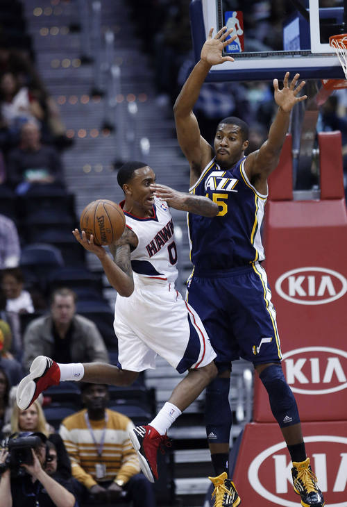Atlanta Hawks point guard Jeff Teague (0) tries to pass as Utah Jazz power forward Derrick Favors (15) defends in the first half of an NBA basketball game on Friday, Jan. 11, 2013, in Atlanta. (AP Photo/John Bazemore)