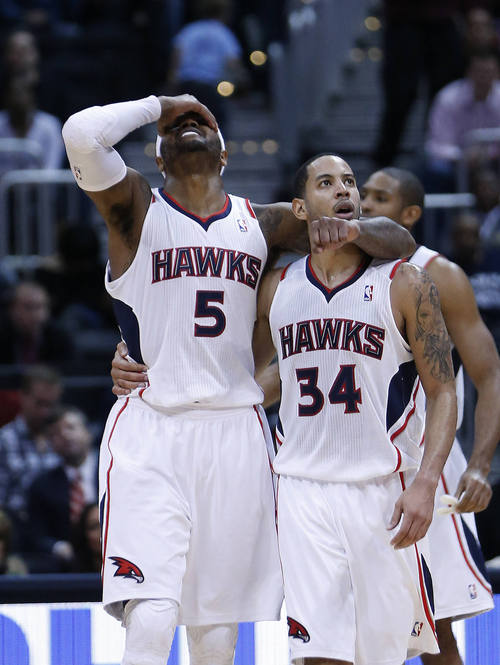 Atlanta Hawks' Devin HArris (34) and Josh Smith (5) react after a foul in the second half of an NBA basketball game against the Utah Jazz, Friday, Jan. 11, 2013, in Atlanta. Atlanta won 103-95. (AP Photo/John Bazemore)