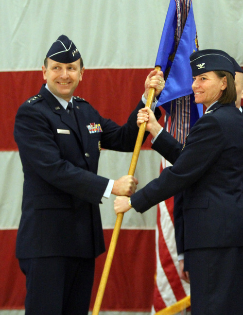 Rick Egan  | The Salt Lake Tribune   Lt. Gen. Bruce A. Litchfield, commander of the Air Force Sustainment Center (AFSC) (left), holds the flag with outgoing commander, Col. Sarah E. Zabel, during the change-of-command ceremony at Hill Air Force Base, Friday, January 11, 2013. Col. Kathryn L. Kolbe assumed command of the 75th Air Base Wing from Col. Sarah E. Zabel.