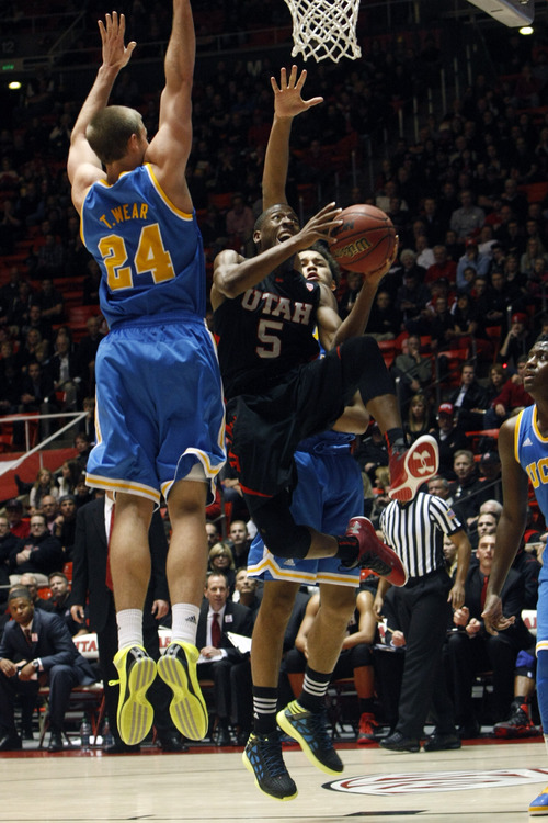 Chris Detrick  |  The Salt Lake Tribune Utah Utes guard Jarred DuBois (5) shoots past UCLA Bruins forward Travis Wear (24) and UCLA Bruins guard Kyle Anderson (5) during the second half of the game at the Huntsman Center Thursday January 10, 2013.  UCLA won the game 57-53.