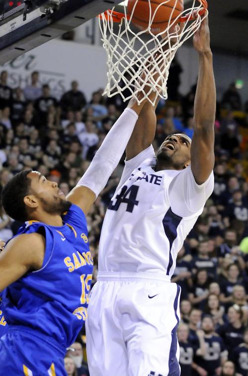 Utah State forward Kyisean Reed (34) dunks the ball on San Jose State forward Chris Cunningham (15) during an NCAA college basketball game Friday, Jan. 11, 2013, in Logan, Utah. (AP Photo/The Herald Journal, Eli Lucero)