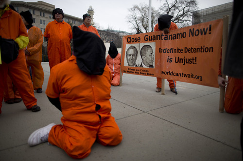 Demonstrators, dressed as detainees, protest against the U.S. military detention facility in Guantanamo Bay, Cuba, in front of the U.S. Supreme Court on Friday, Jan. 11, 2013 in Washington. The protest marks the 11th anniversary of the first detainees being jailed at Guantanamo Bay. (AP Photo/ Evan Vucci)