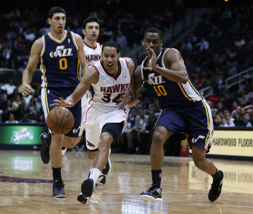 Atlanta Hawks point guard Devin Harris (34) drives as Utah Jazz point guard Alec Burks (10) and center Enes Kanter (0) defend in the second half of an NBA basketball game Friday, Jan. 11, 2013, in Atlanta. Atlanta won 103-95. (AP Photo/John Bazemore)