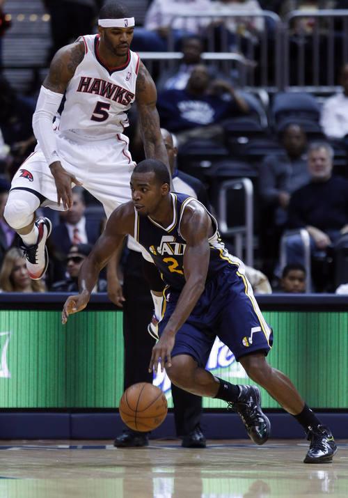 Utah Jazz power forward Paul Millsap (24) drives to the basket as Atlanta Hawks small forward Josh Smith (5) defends in the second half of an NBA basketball game on Friday, Jan. 11, 2013, in Atlanta. Atlanta won 103-95. (AP Photo/John Bazemore)