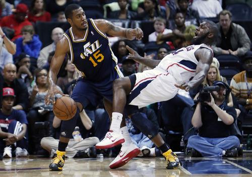 Utah Jazz power forward Derrick Favors (15) fouls Atlanta Hawks power forward Ivan Johnson in the second half of an NBA basketball game on Friday, Jan. 11, 2013, in Atlanta.  Atlanta won 103-95. (AP Photo/John Bazemore)